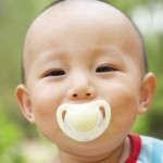 cute baby with pacifier in mouth